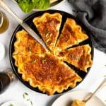top down view on sliced Quiche Lorraine on a set table with salad