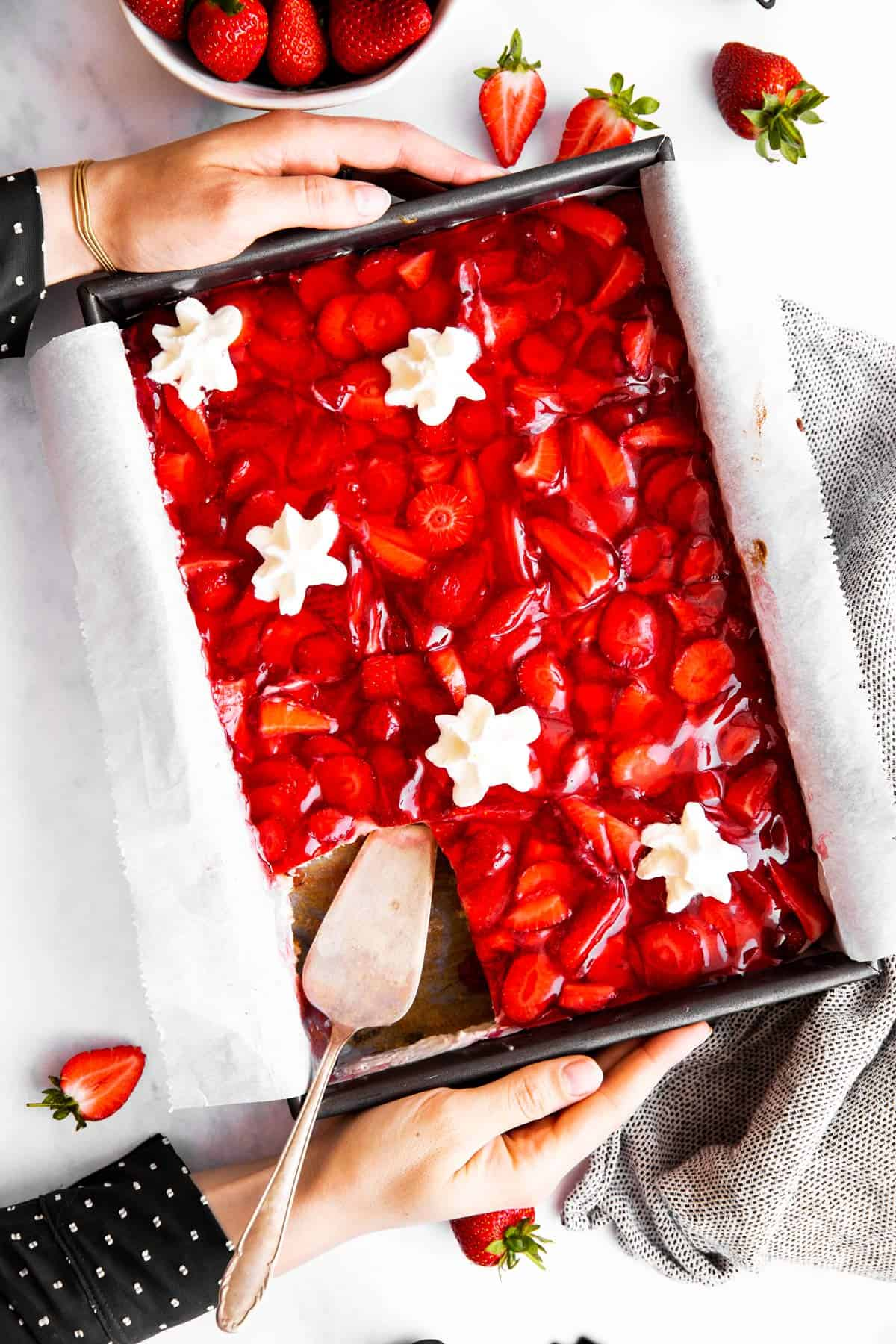 top down view on female hands holding cake pan with strawberry cake