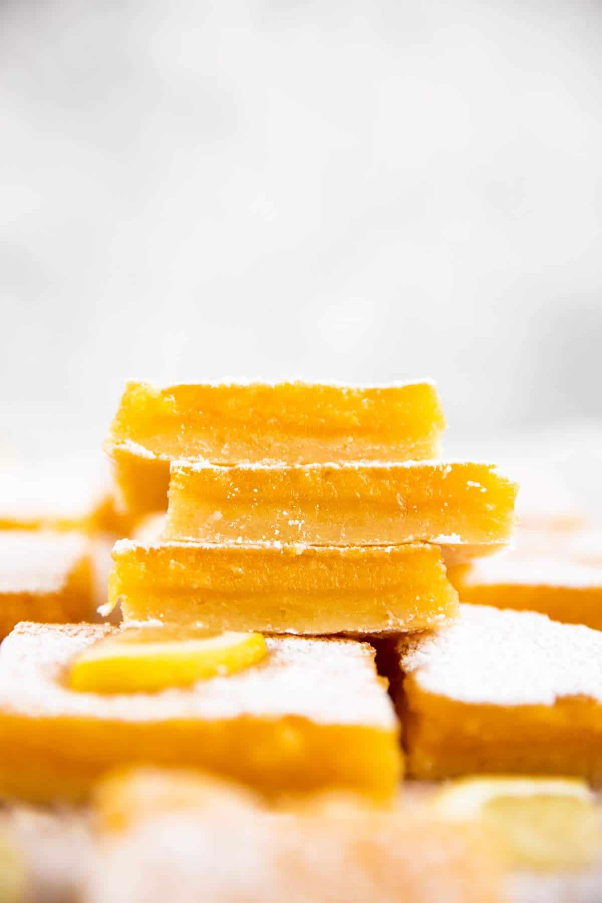 stack of lemon bars on more lemon bars