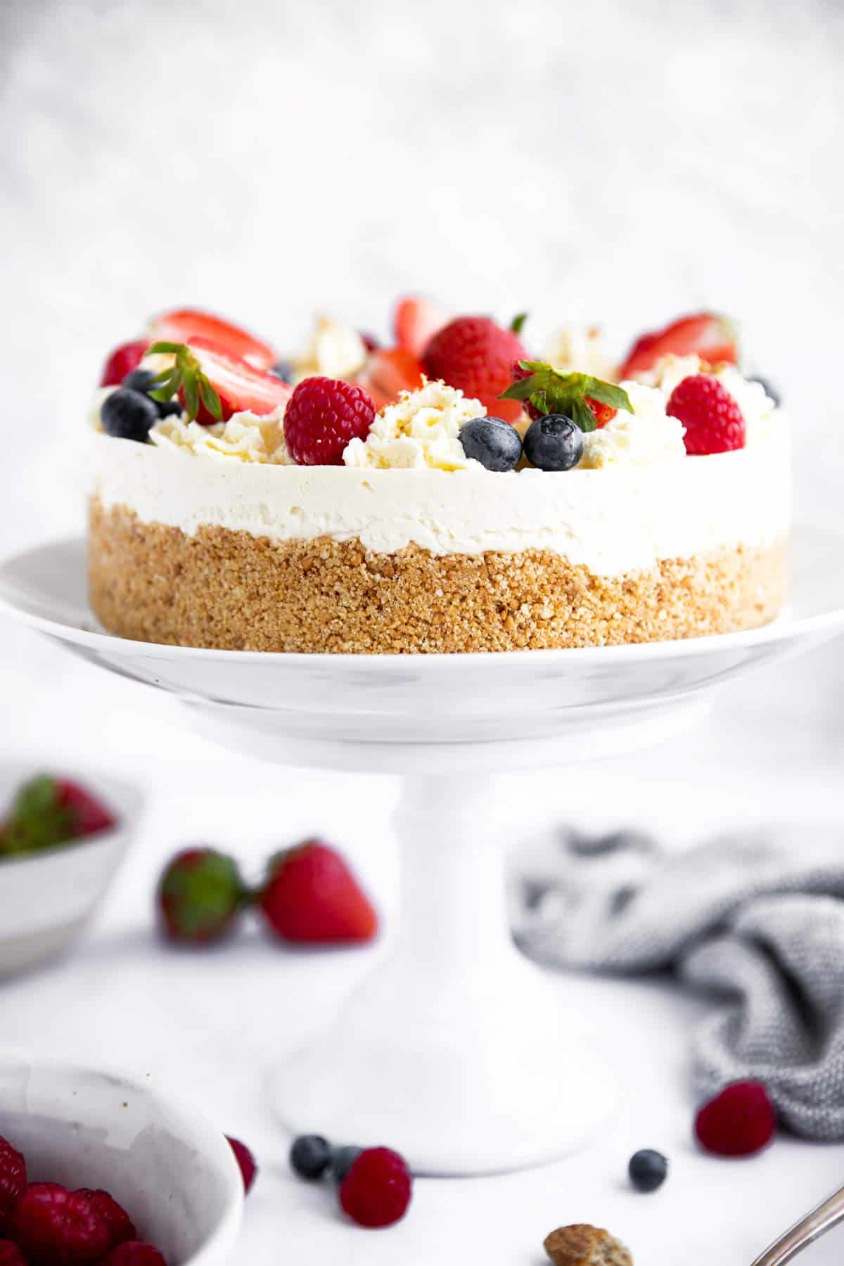no bake cheesecake decorated with berries on a cake stand