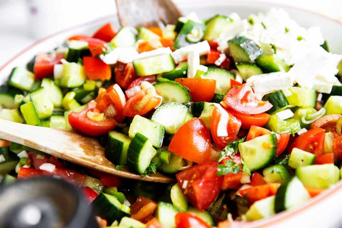 close up photo of salad tongs tossing a Shopska salad
