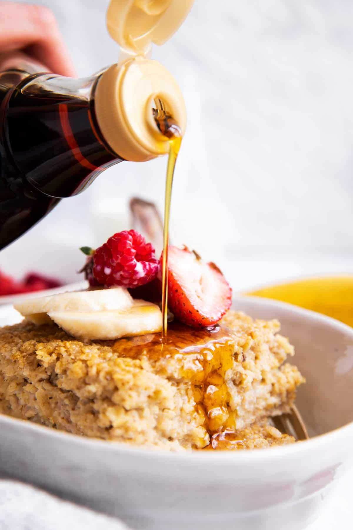 pouring maple syrup over baked oatmeal in a white bowl with fresh fruit