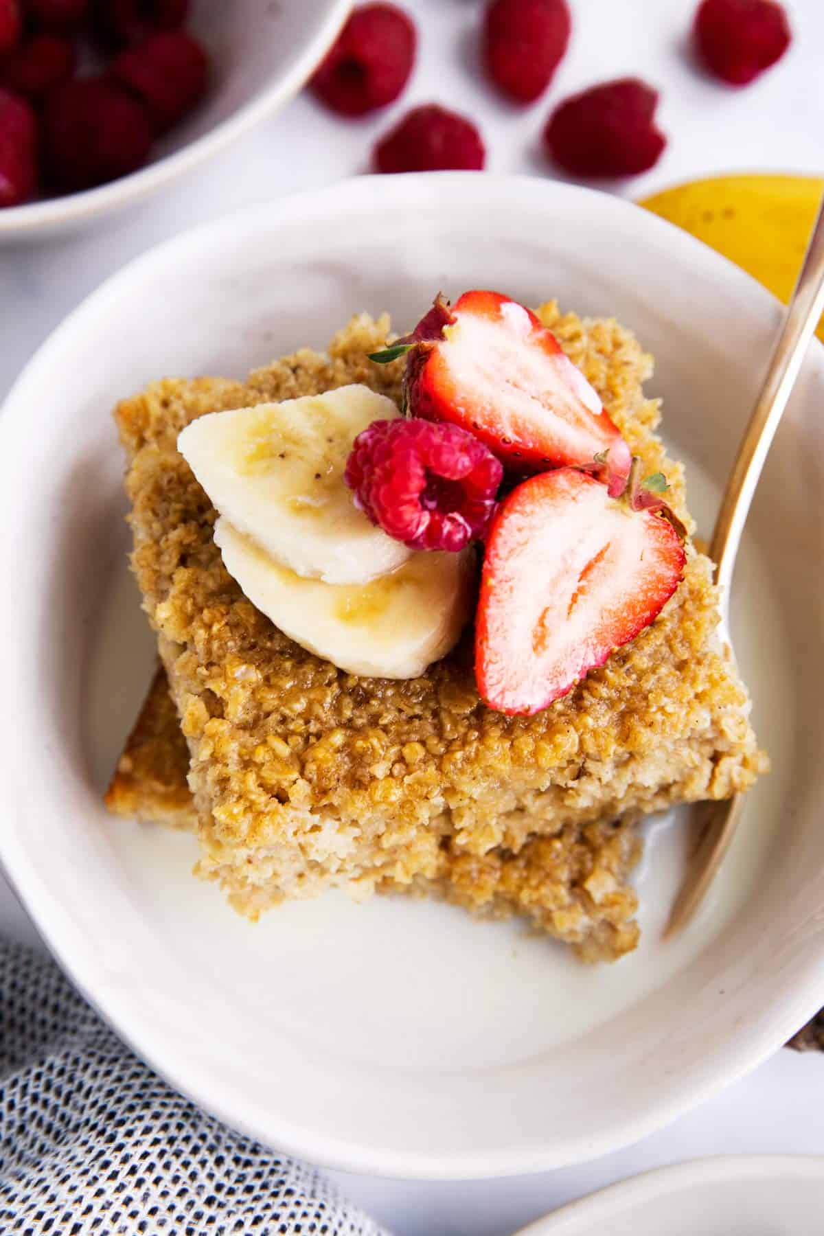 baked oatmeal and fruit in a bowl with milk