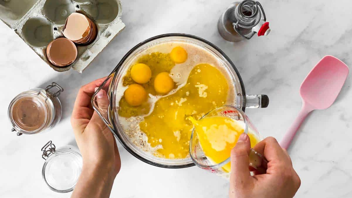 pouring melted butter into bowl with eggs and oats
