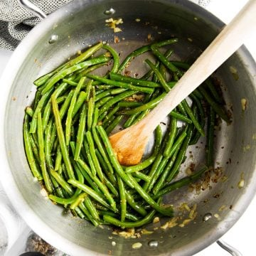 skillet with sautéed green beans and wooden spoon
