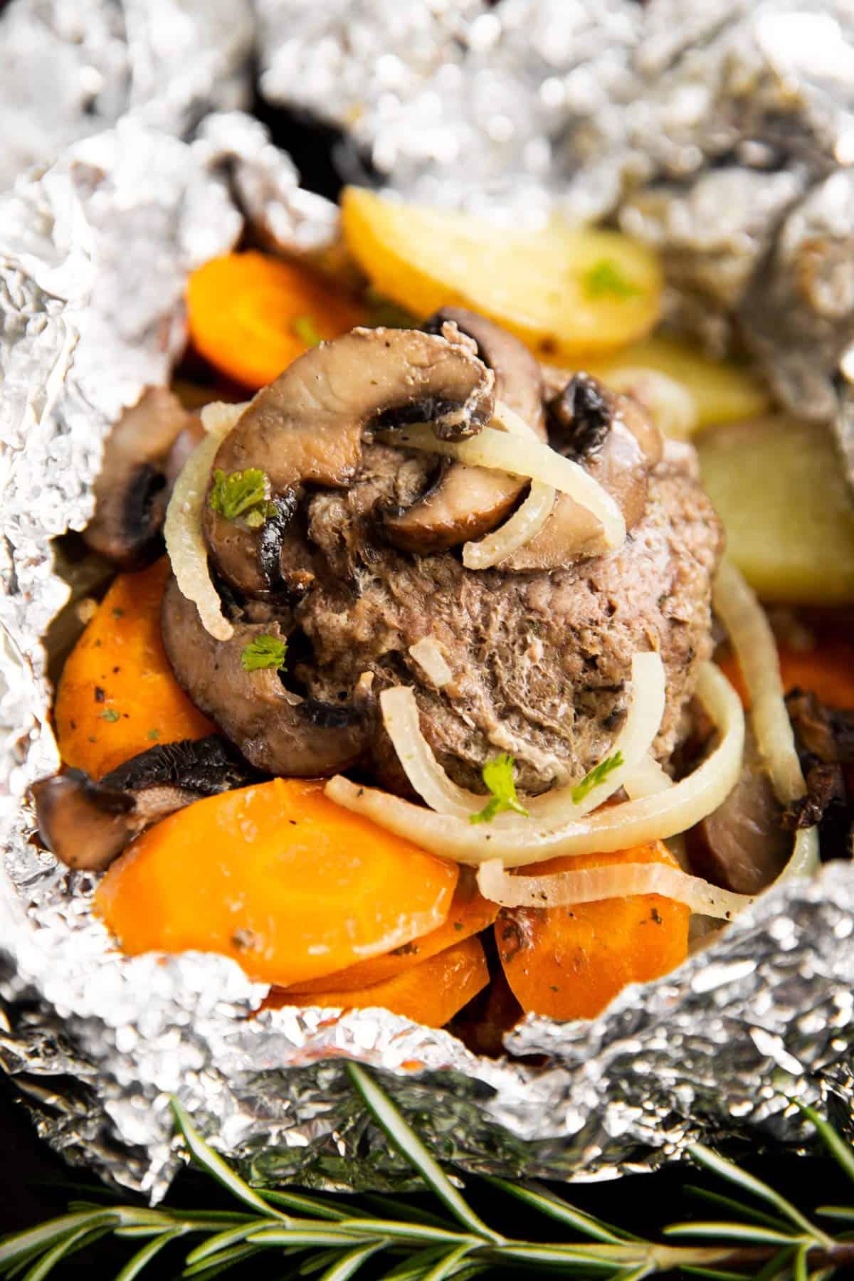 hamburger patty on carrots with mushroom and onions