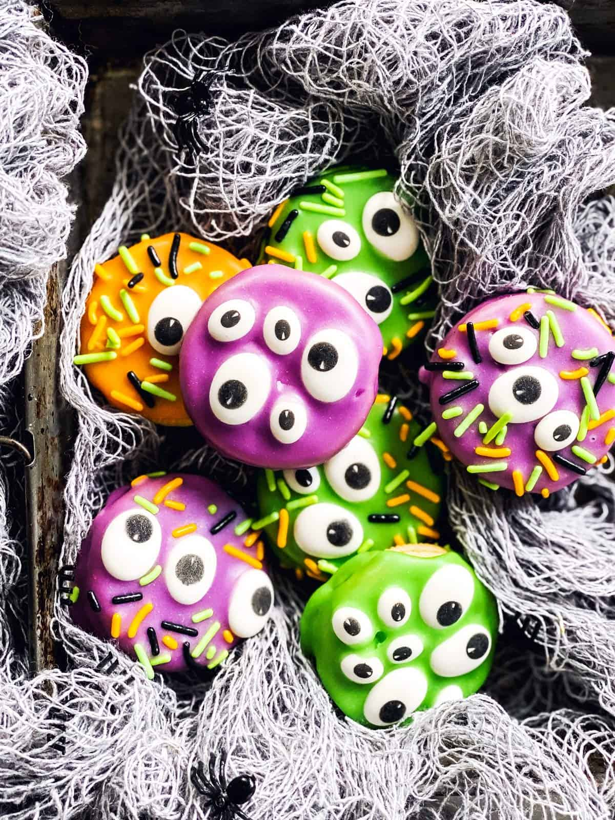 monster decorated Oreo cookies in fake spider webbing