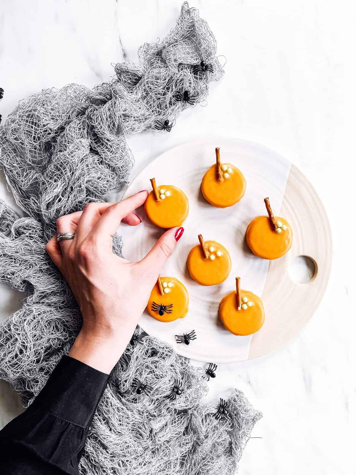 female hand grabbing a pumpkin decorated Oreo off a platter