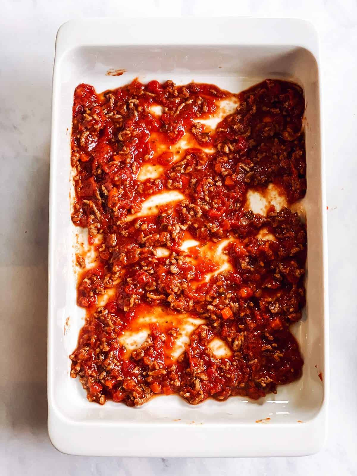 casserole dish with sauce at the bottom