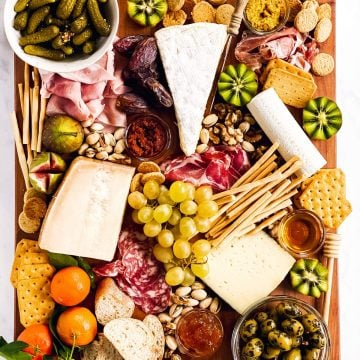 overhead view of a charcuterie board with various cold cuts, cheeses and nibbles