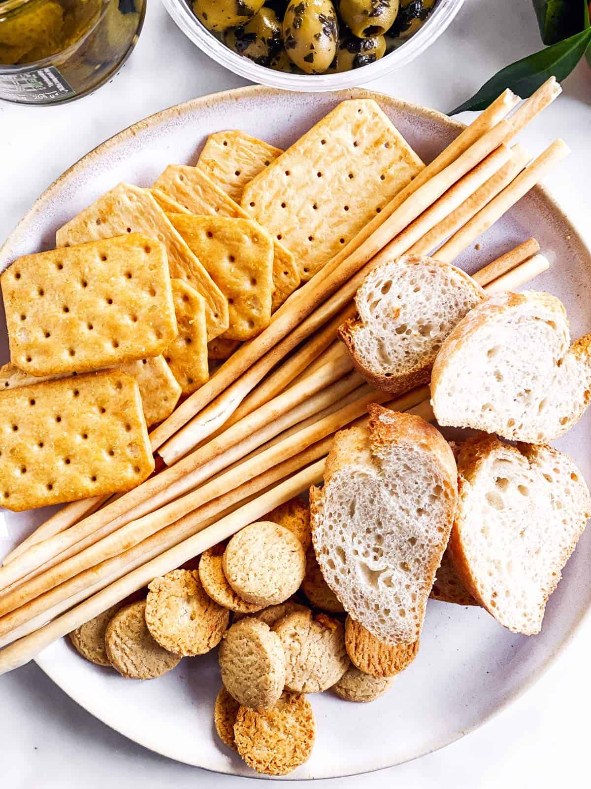 several crackers and sliced baguette on white plate