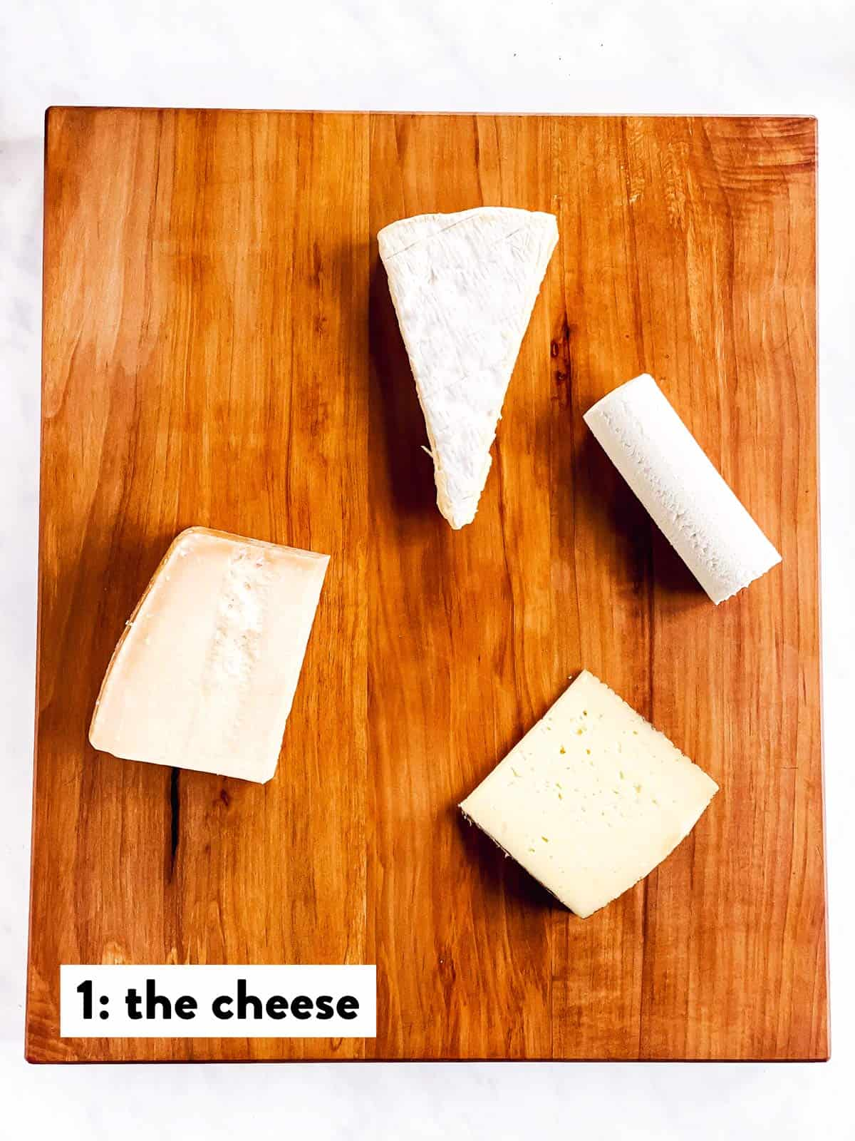 four types of cheese on a wooden board