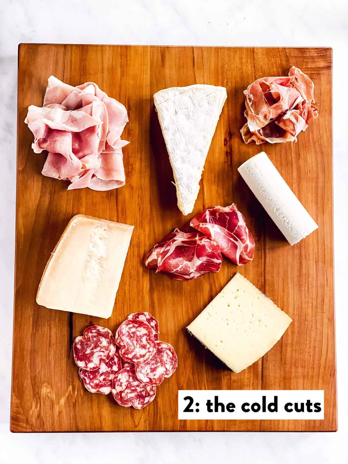 four types of cheese and cold cuts on a wooden board