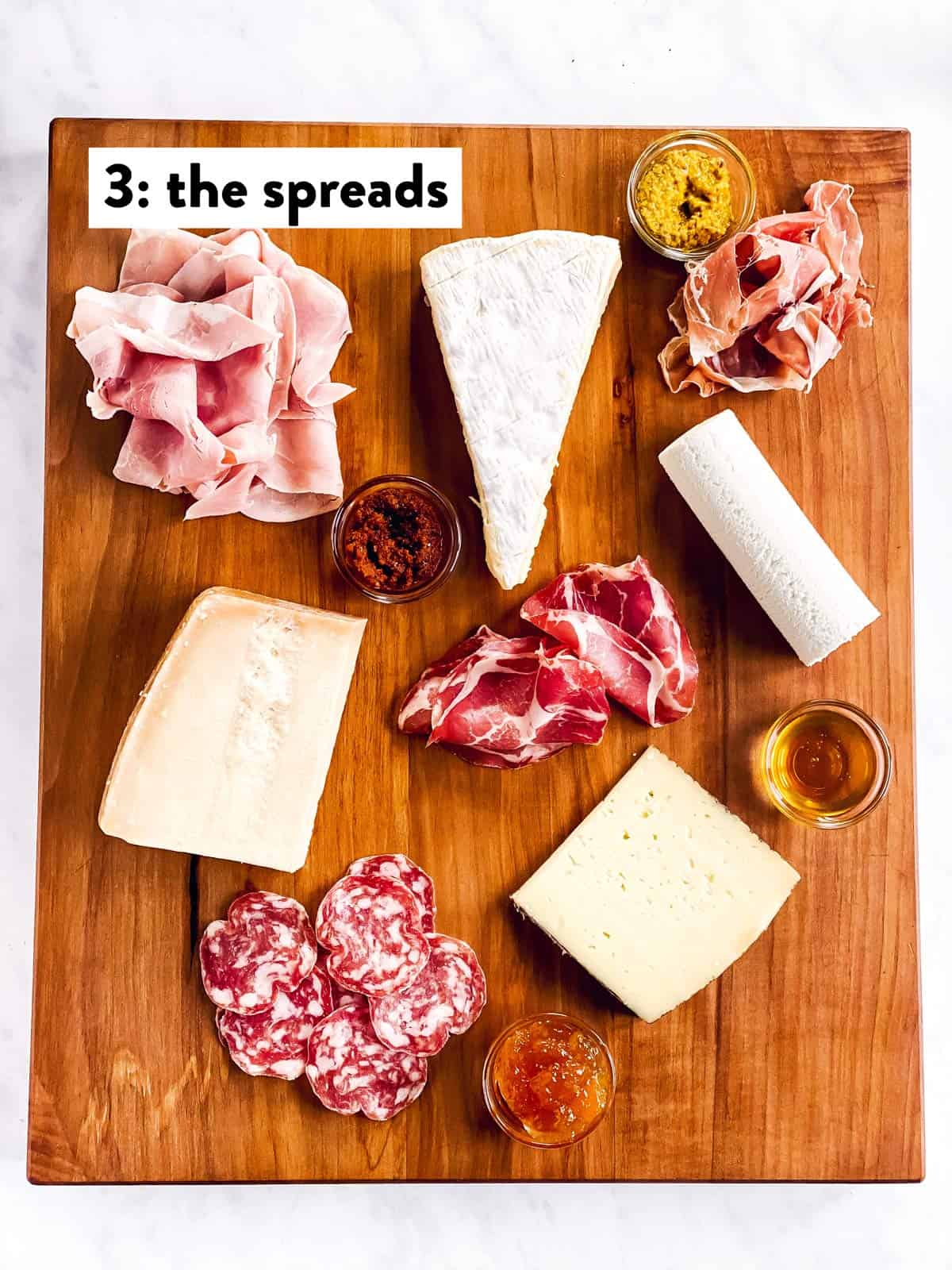 four types of cheese, cold cuts and spreads on a wooden board