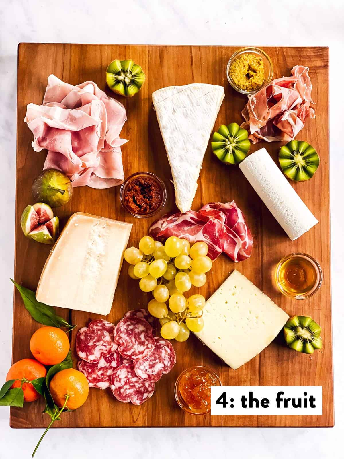 four types of cheese, cold cuts, spreads and fruit on a wooden board