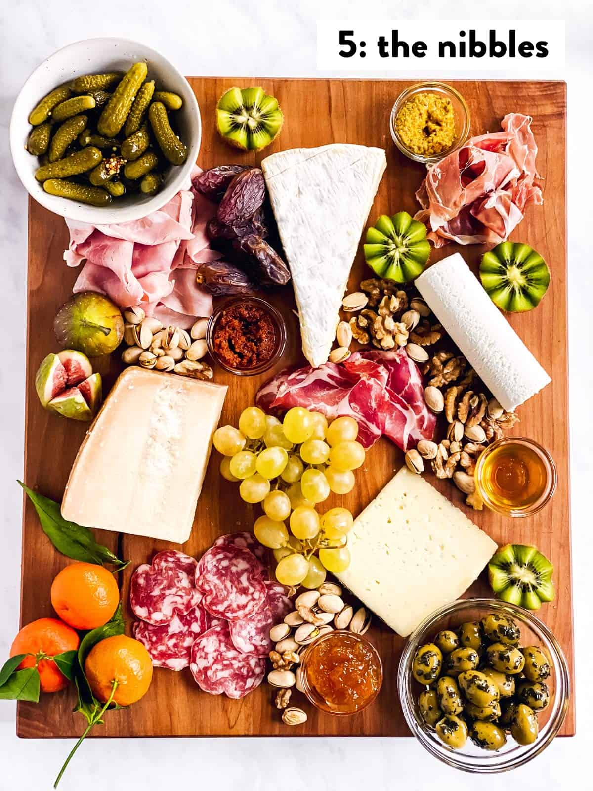 four types of cheese, cold cuts, spreads, fruit and nibbles on a wooden board