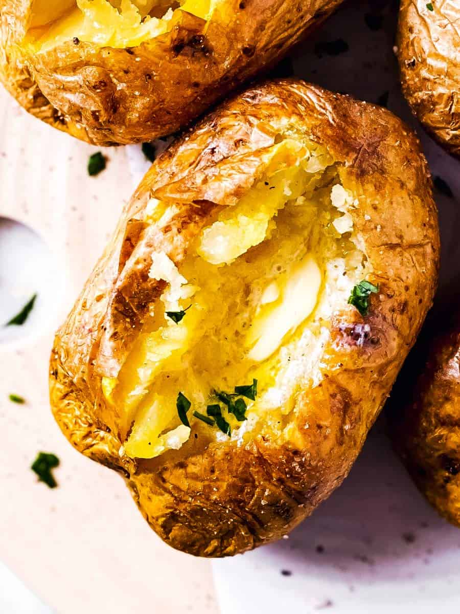 close up photo of air fryer baked potato with butter