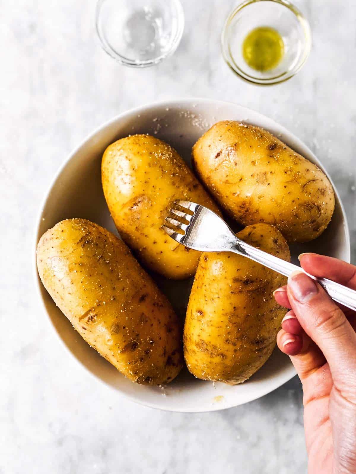 fork pricking a russet potato
