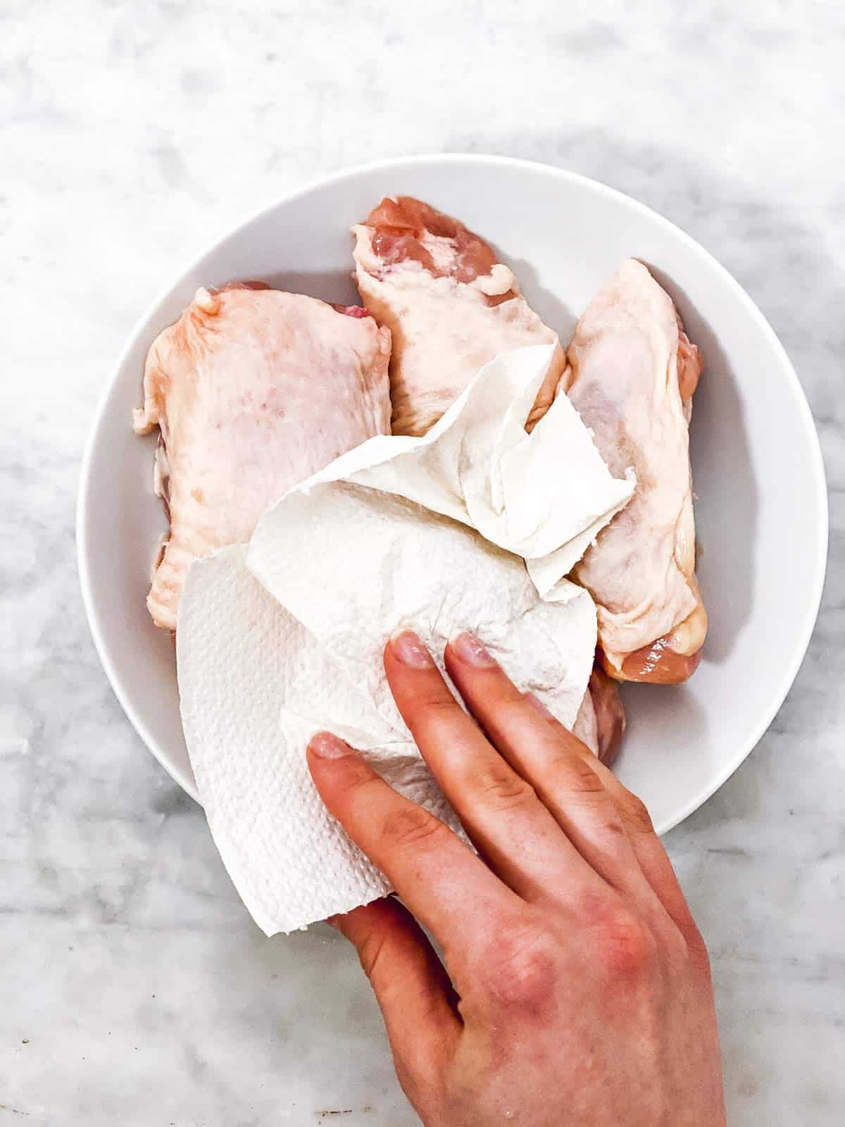 female hand patting dry chicken thighs with paper towels