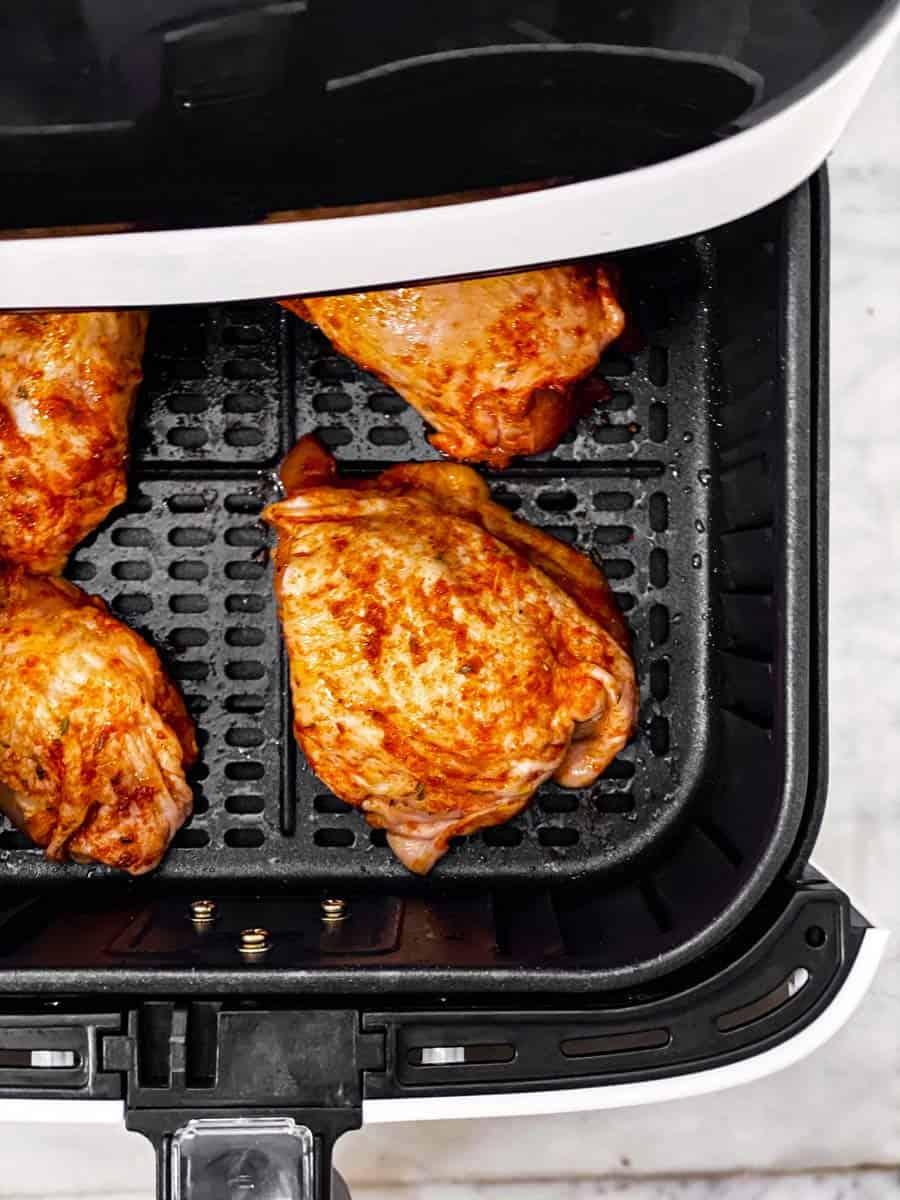 raw seasoned chicken thighs in air fryer basket