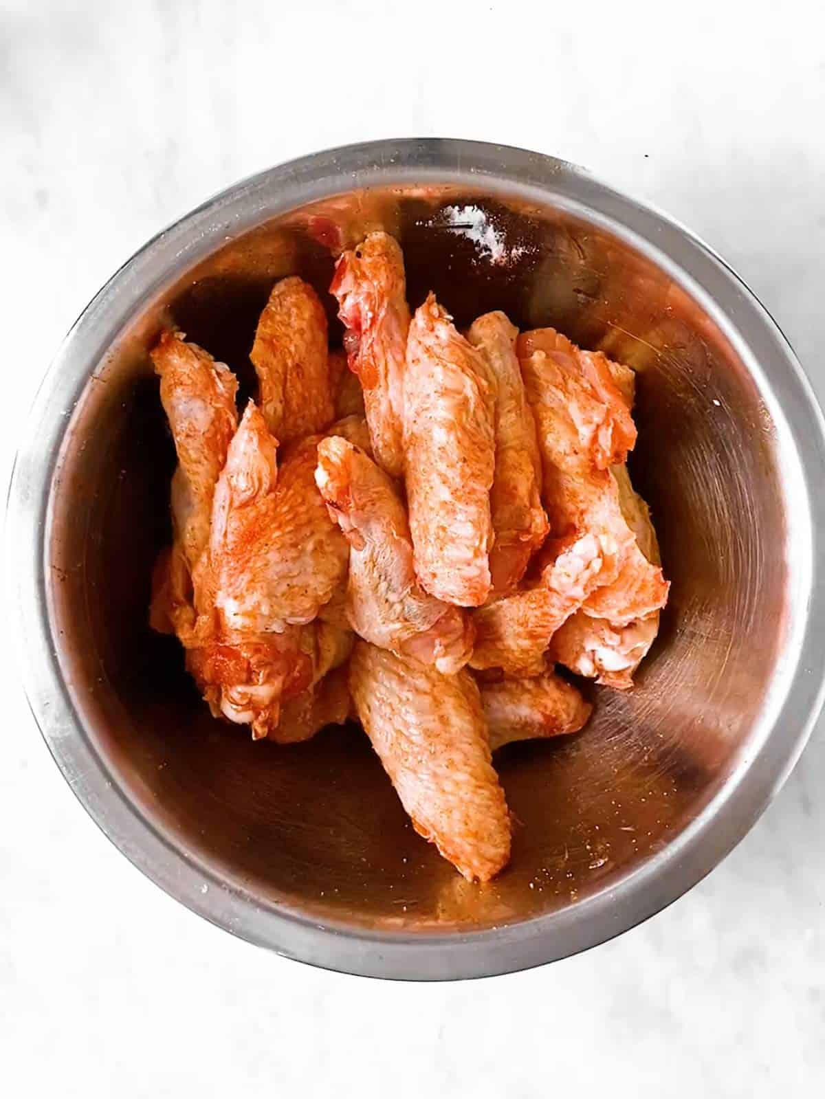 bowl with seasoned raw chicken wings