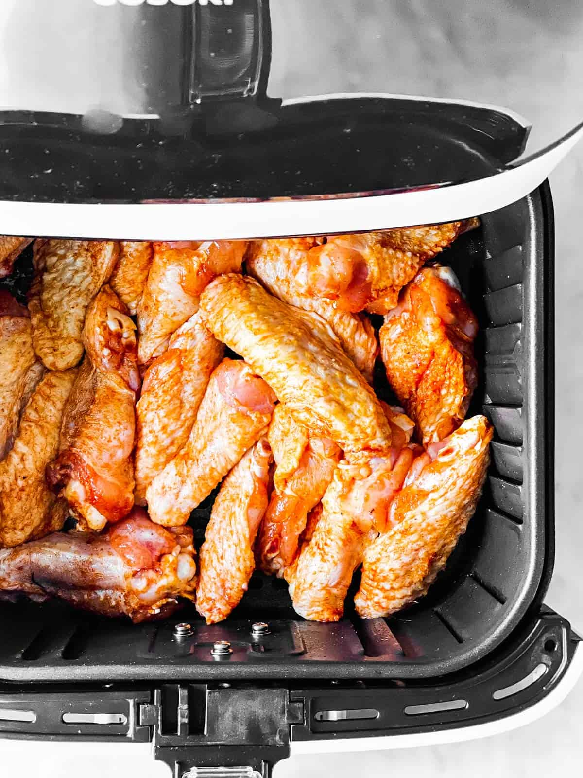 overhead view of raw chicken wings in air fryer basket