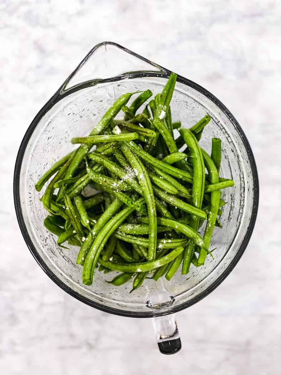glass bowl with seasoned raw green beans