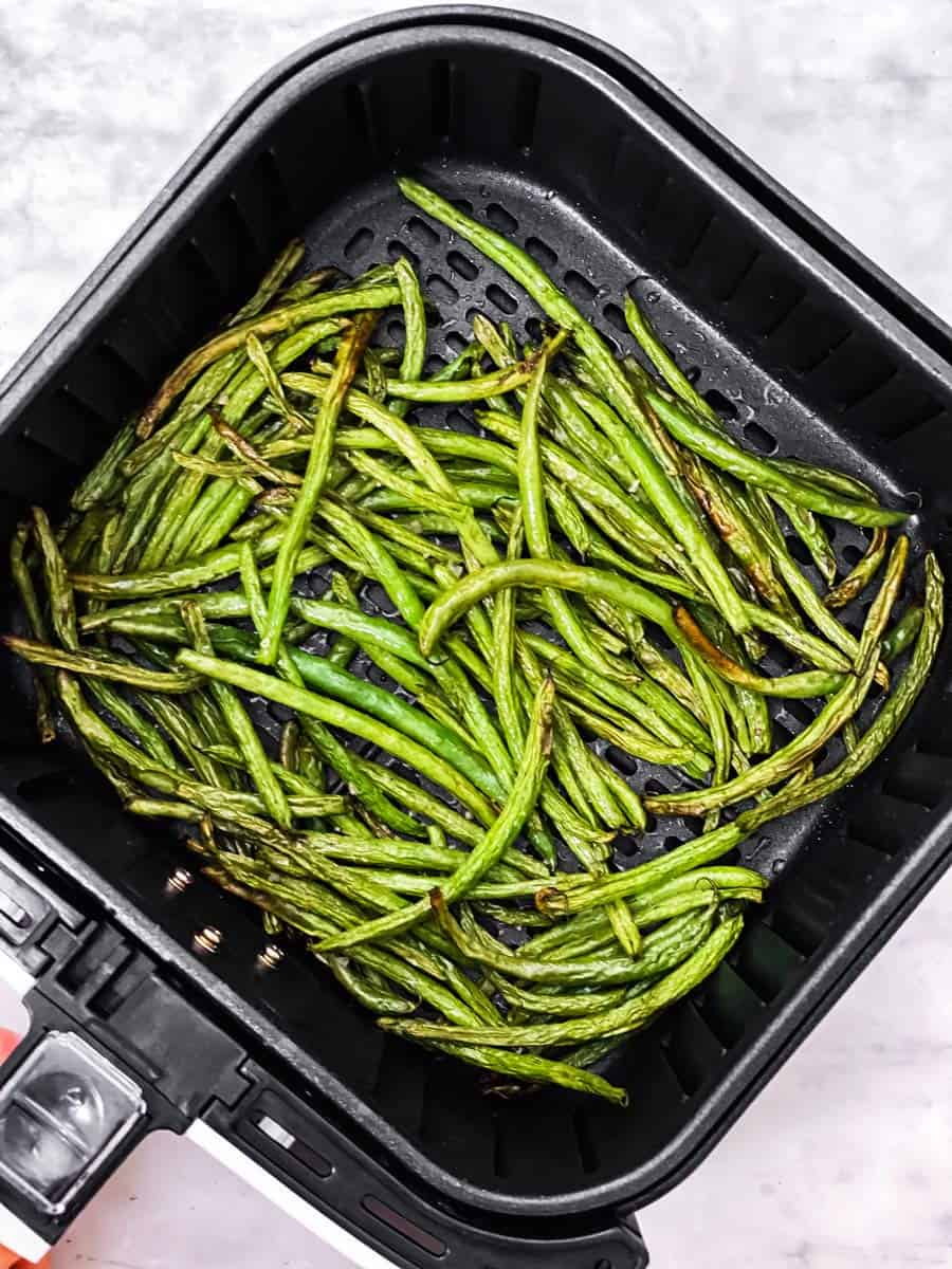 overhead view of air fryer basket filled with cooked green beans
