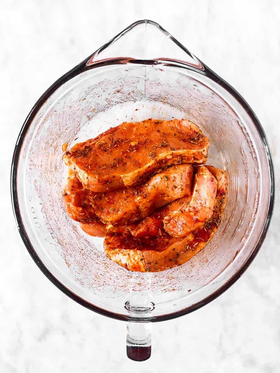 seasoned pork chops in glass bowl
