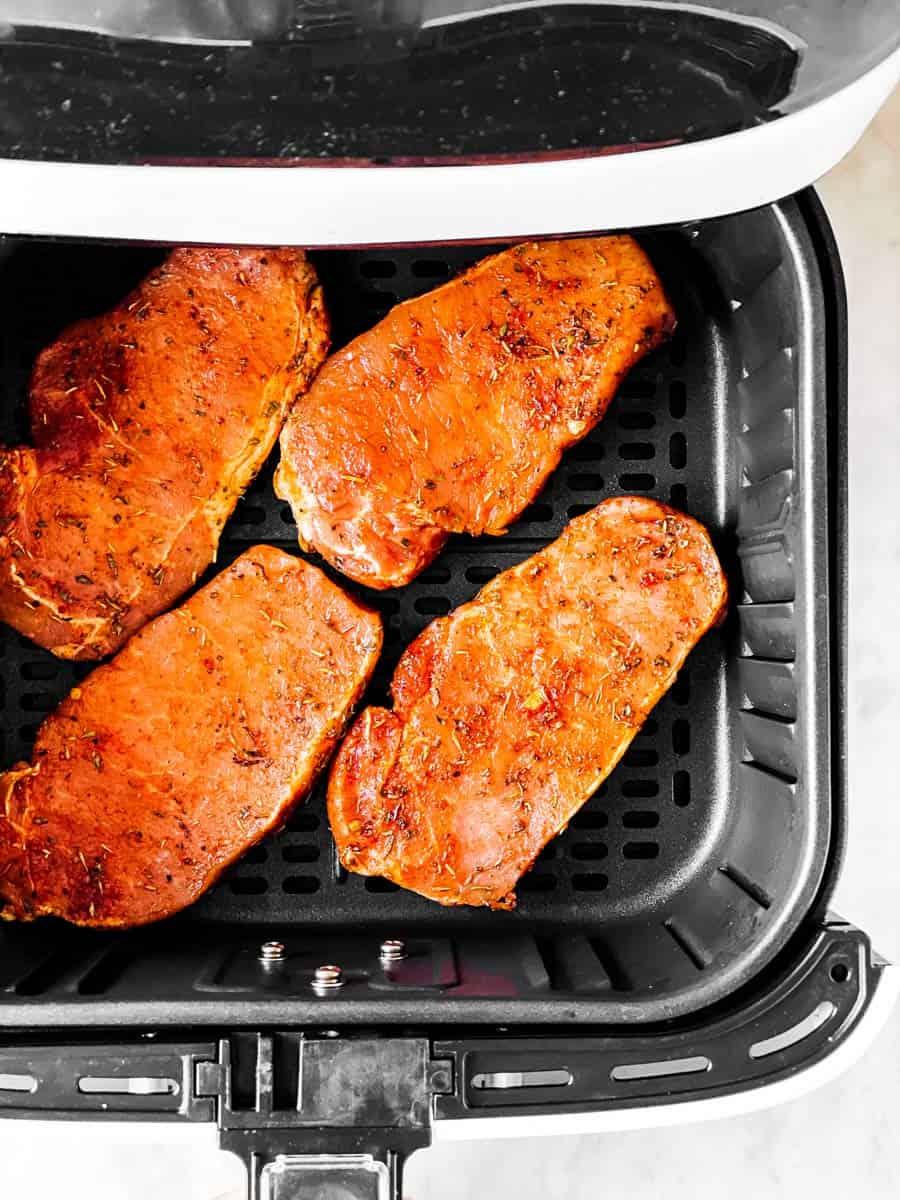 raw seasoned pork chops in air fryer basket