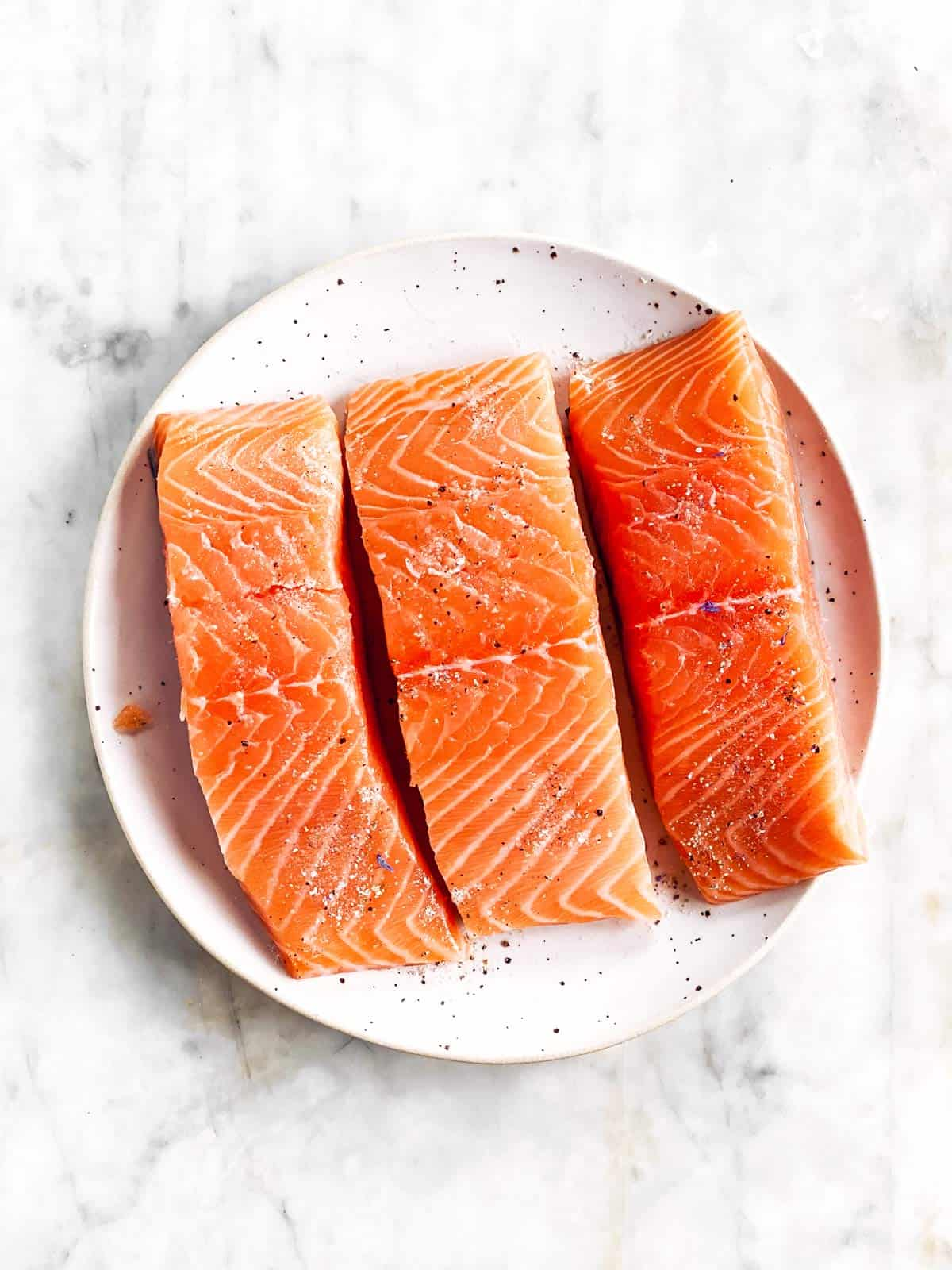 there raw salmon fillets on white plate