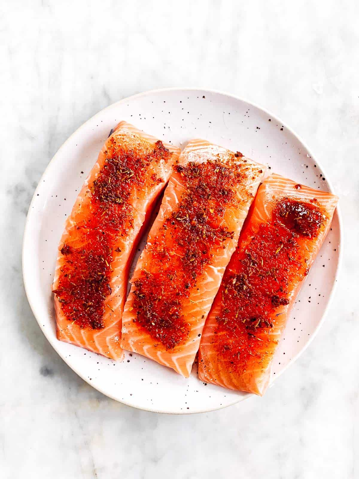 there seasoned raw salmon fillets on white plate