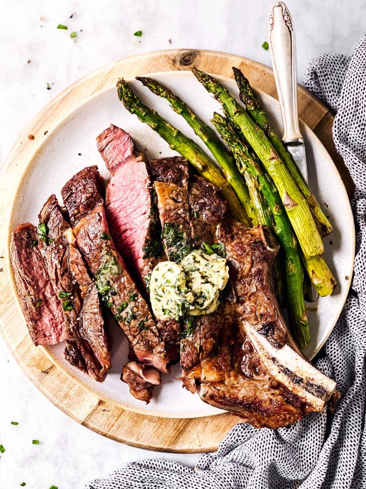 sliced steak on platter with asparagus