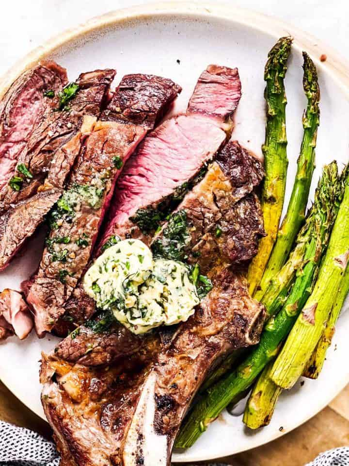 close up photo of sliced steak with garlic herb butter and asparagus on white plate