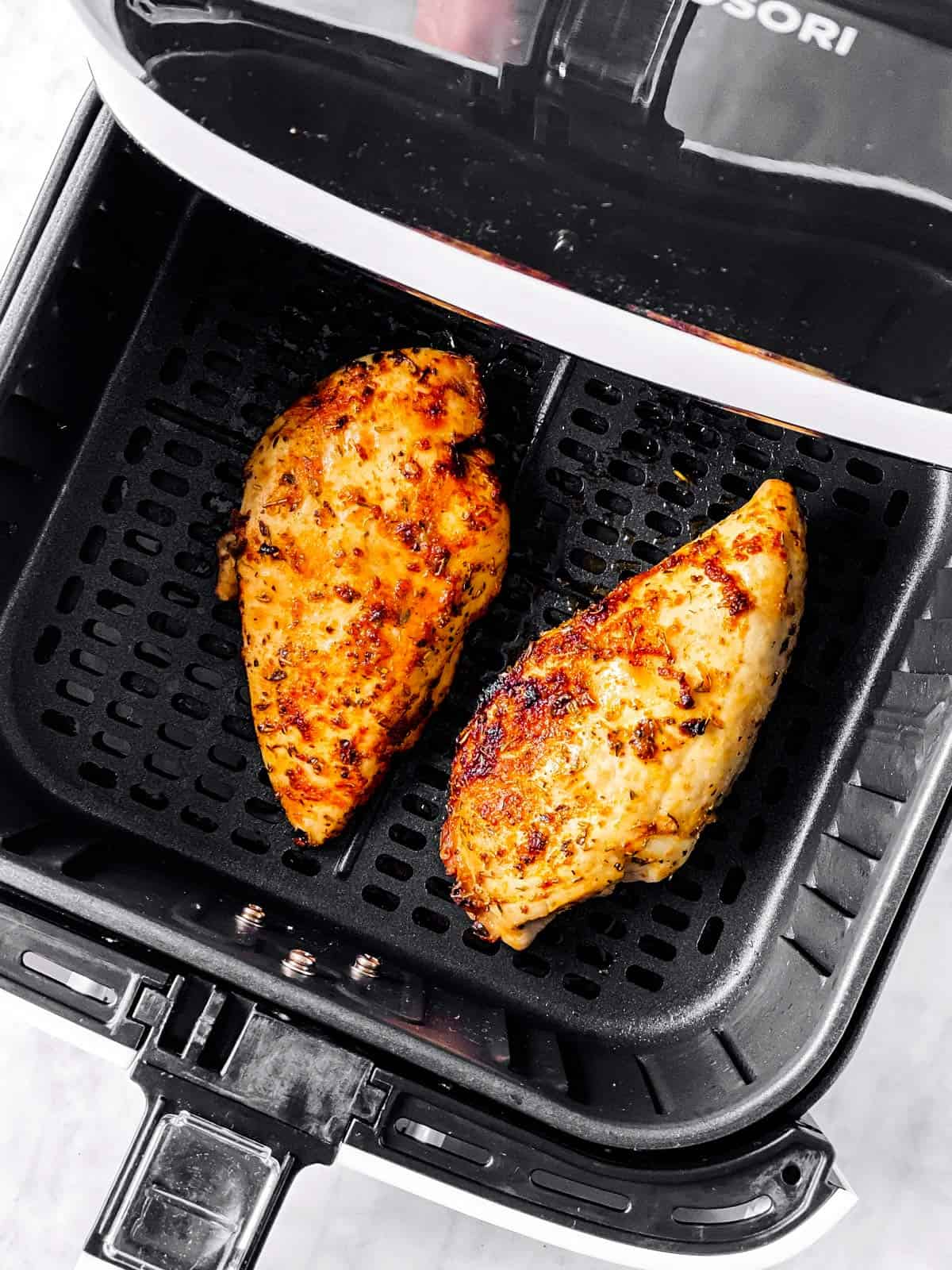 overhead view of air fryer basket with two cooked chicken breasts inside