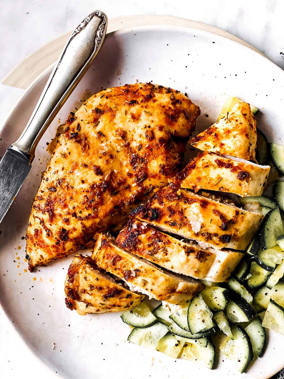 overhead view of sliced airy fryer chicken breasts on white plate with cucumber salad