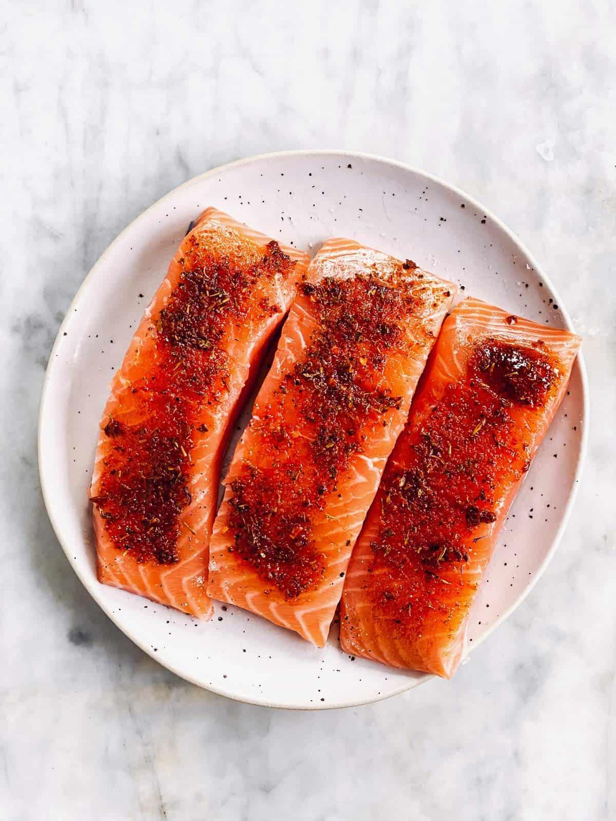 seasoned raw salmon fillets on white plate