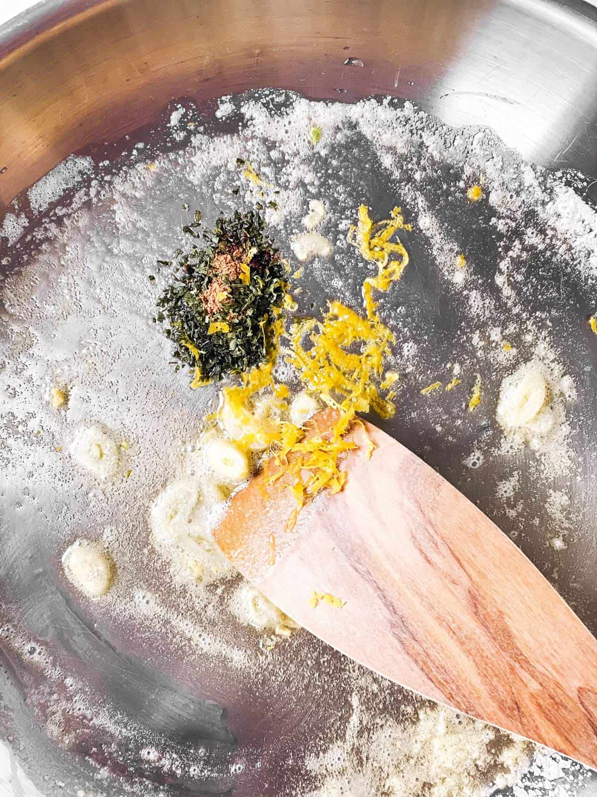 aromatics in butter in skillet with wooden spoon