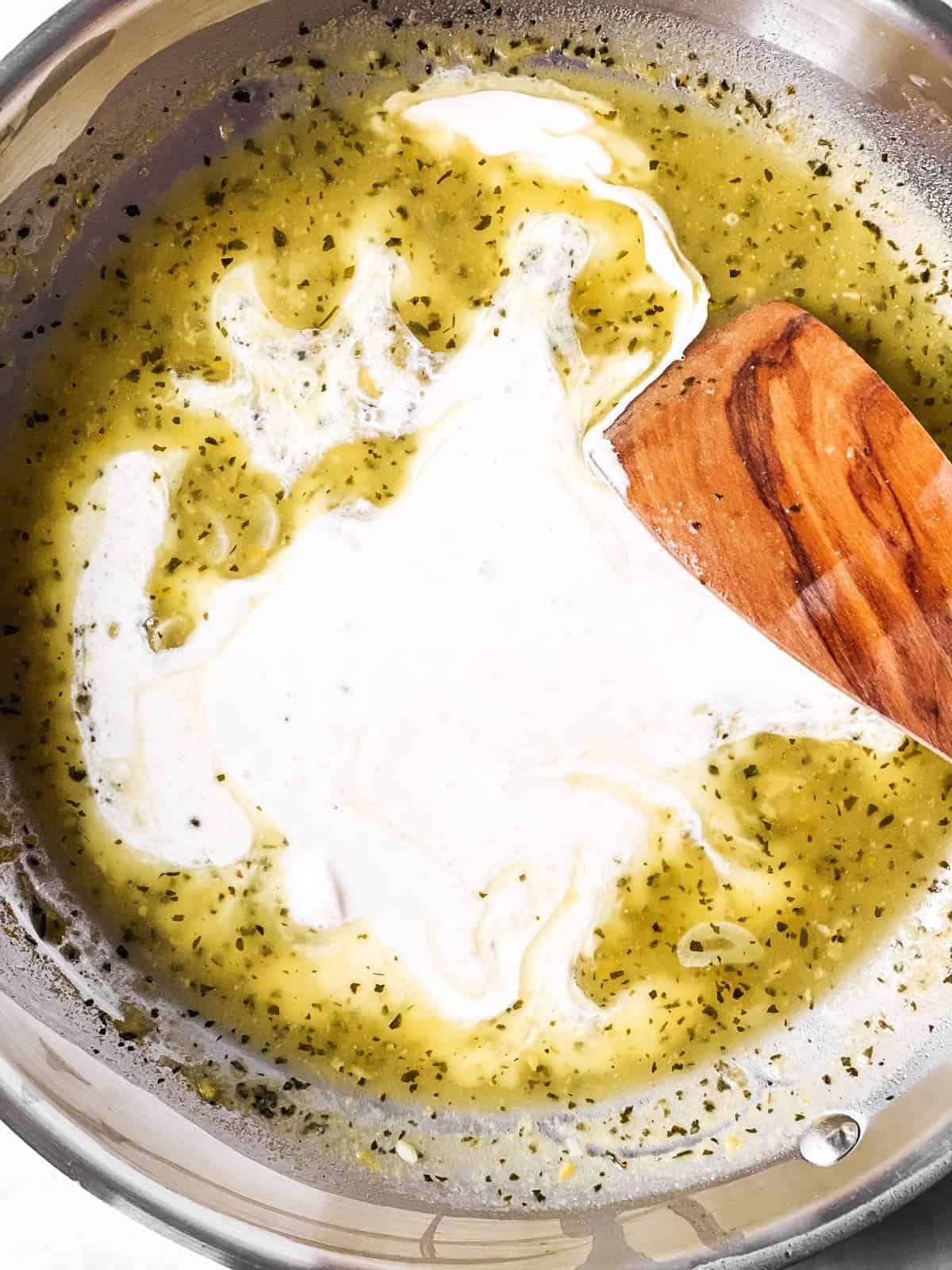 cream stirred into white wine sauce with wooden spoon