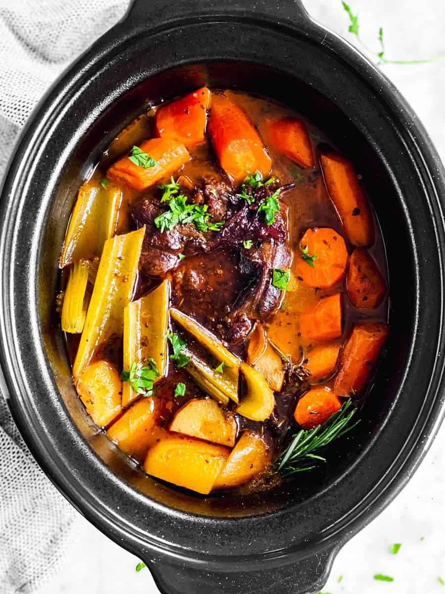 overhead view of black crock with cooked pot roast inside