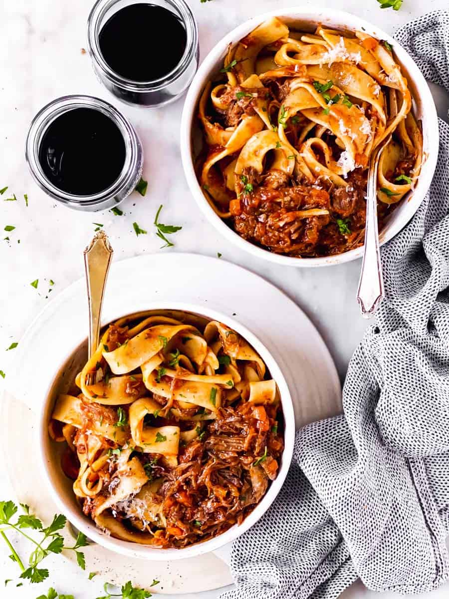 two plates with short rib ragu and pappardelle on marble surface