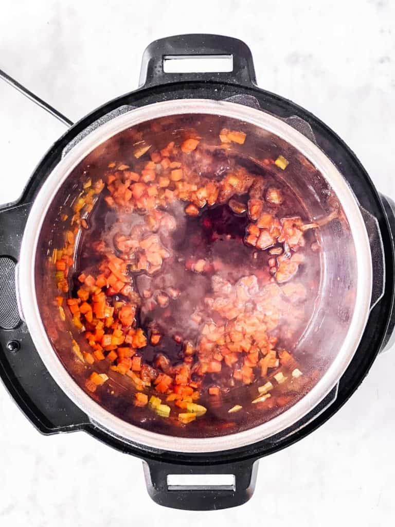 overhead view of instant pot with mirepoix and red wine