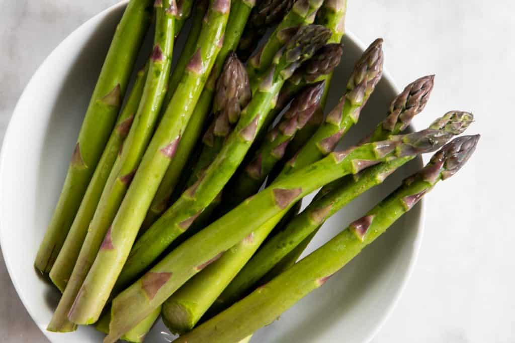 trimmed asparagus in white plate
