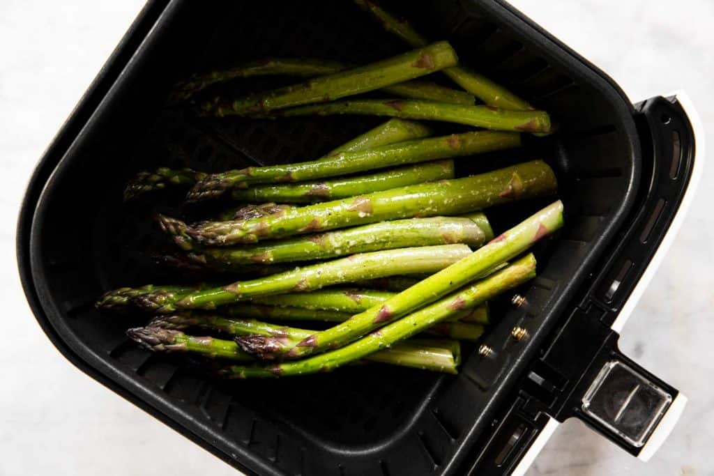 raw asparagus in air fryer basket