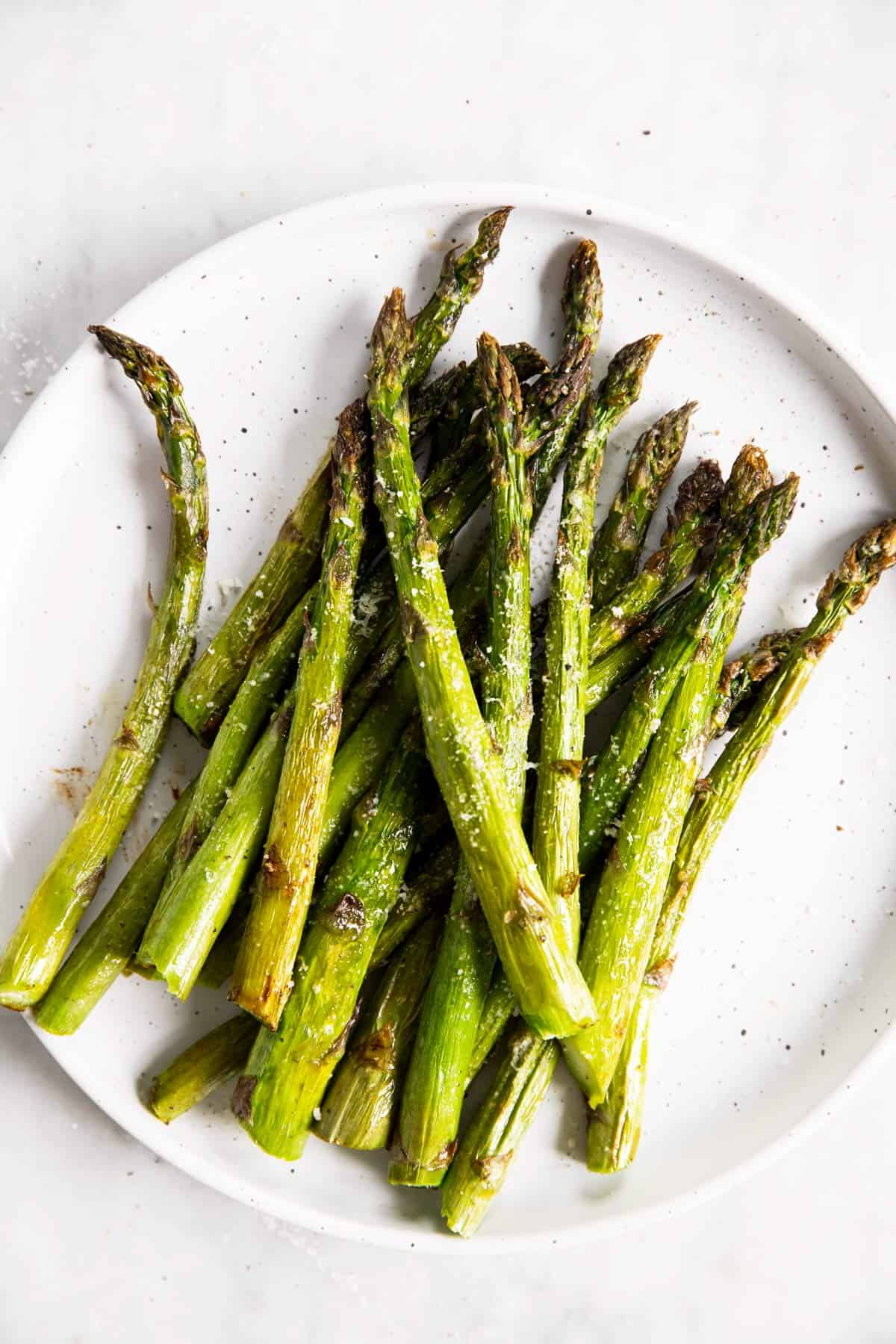 overhead view of air fried asparagus on white plate