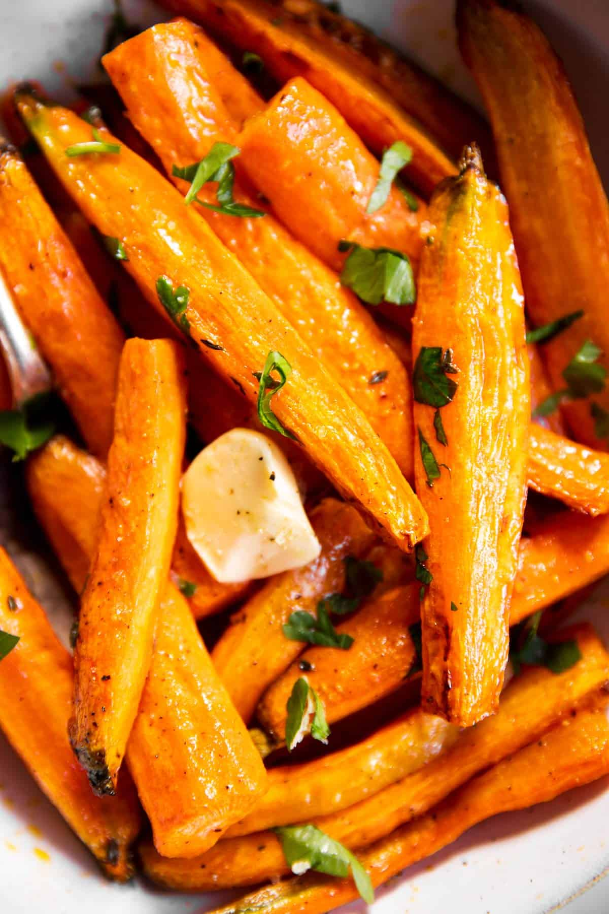close up photo of air fryer carrots in bowl with butter
