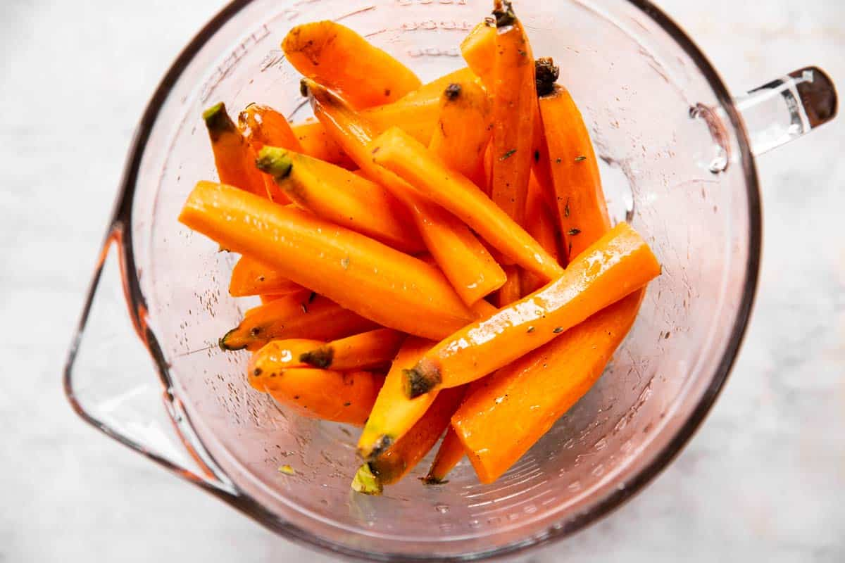 glass bowl with raw carrots tossed in oil and seasoning