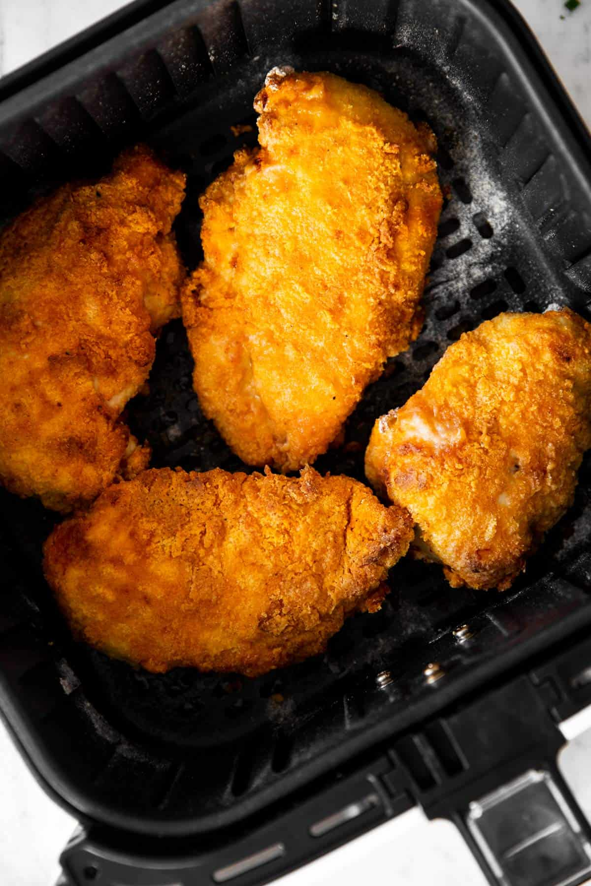 overhead view of fried chicken in air fryer basket
