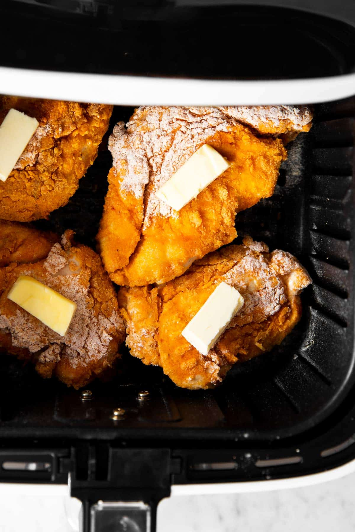half cooked fried chicken in air fryer basket topped with butter