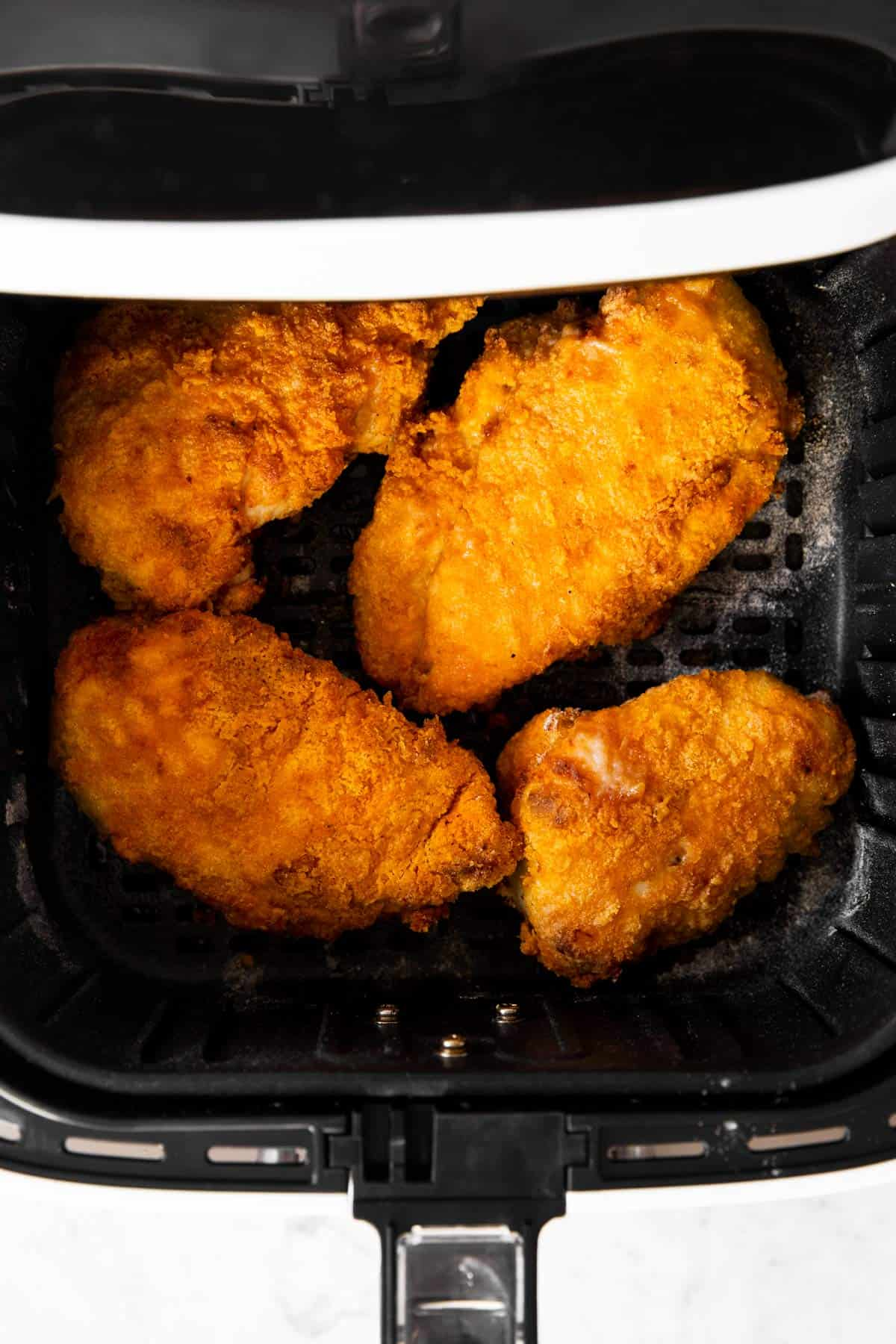 overhead view of four pieces of fried chicken in air fryer basket